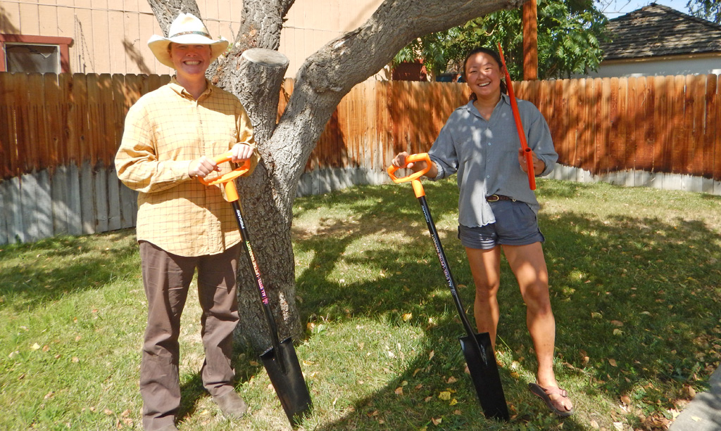 man and woman posing with shovels under a tree